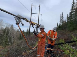 Two PowerNorth Workers at a Power Line